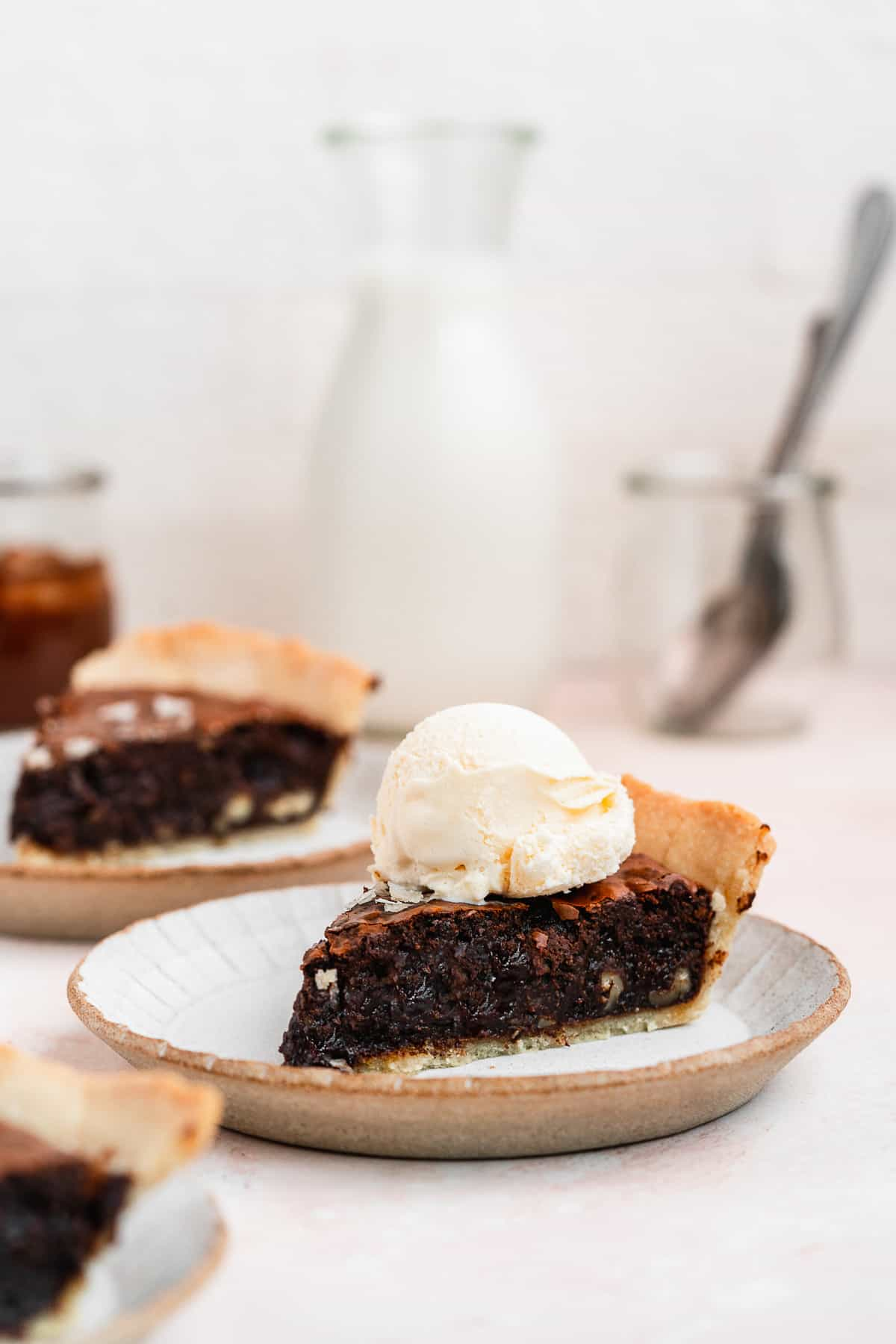 Side close up of a single pie slice on a small grey plate served a la mode with a scoop of vanilla ice cream on top.   Additional slices are on plates in the background.