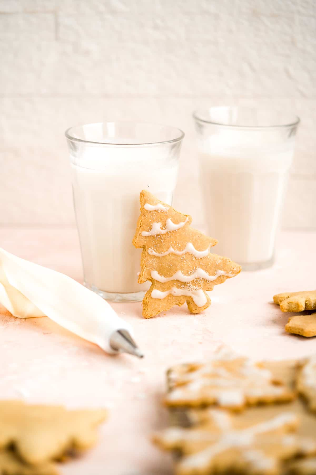 A single Soft and Crispy Gluten-free Sugar Cookie leaning against two clear glasses of milk.  Additional cookies are arranged around the glasses.