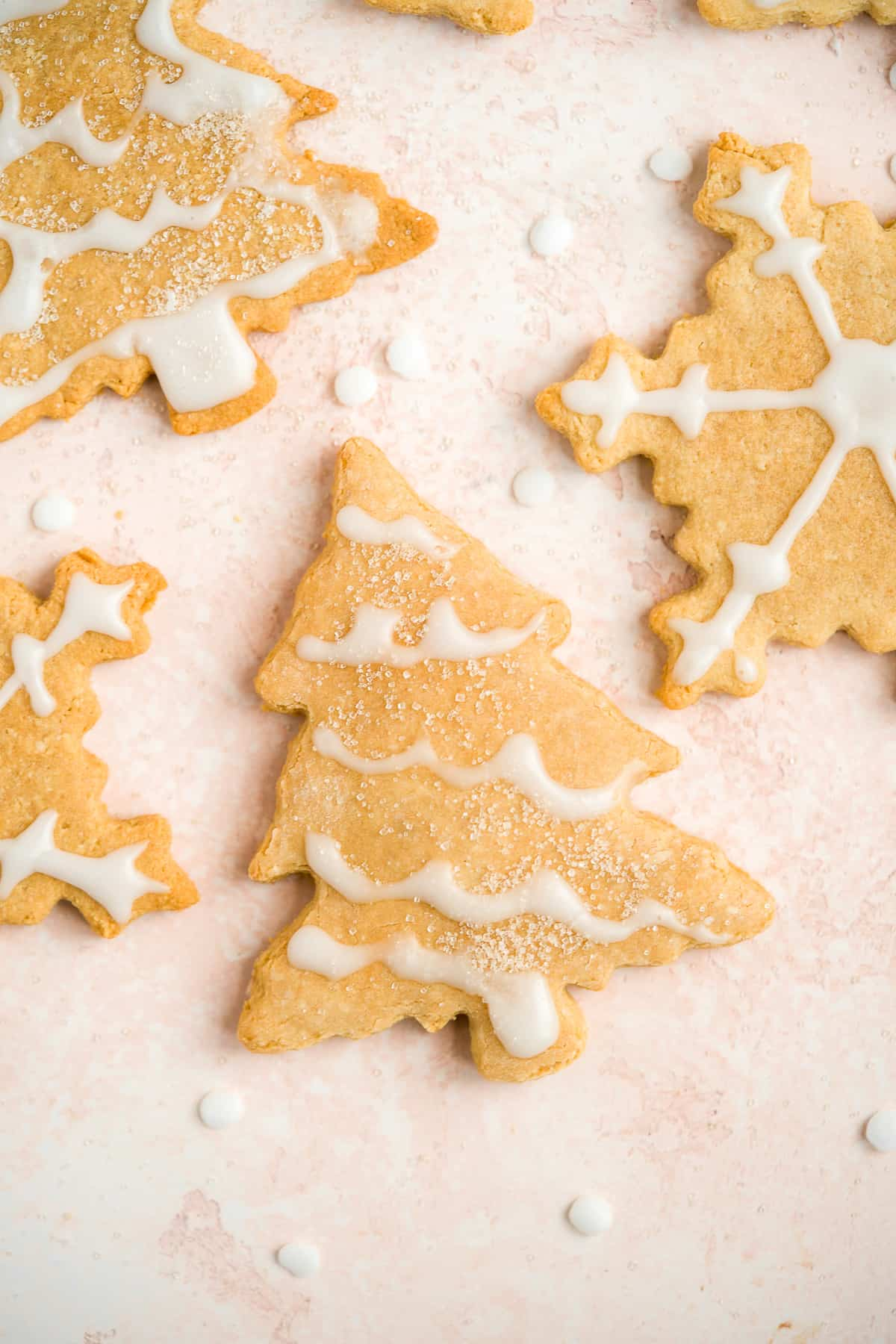 Close up photo of snowflake and Christmas tree shaped cookies with white icing.