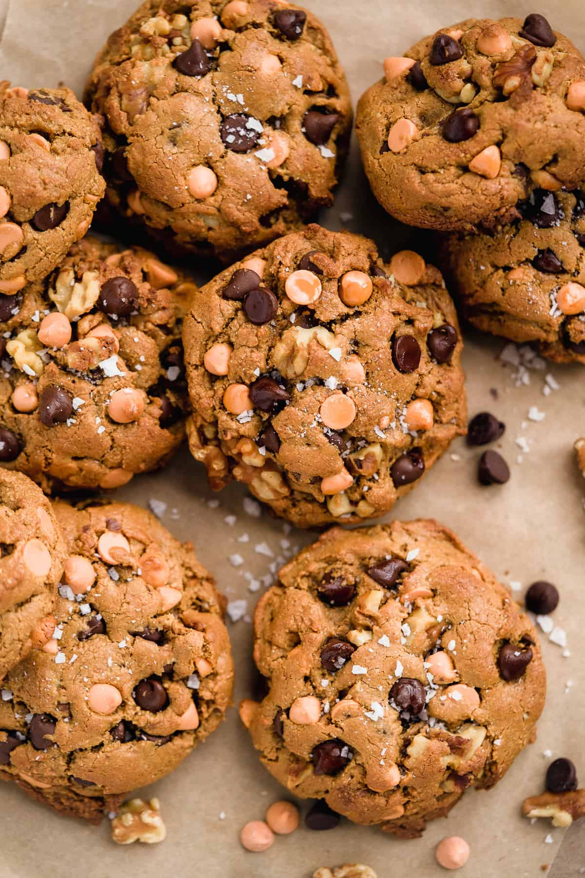 Closeup photo of 8-9 butterscotch chocolate chip cookies scattered on parchment paper.  Chocolate chips and sea salt are sprinkled nearby.