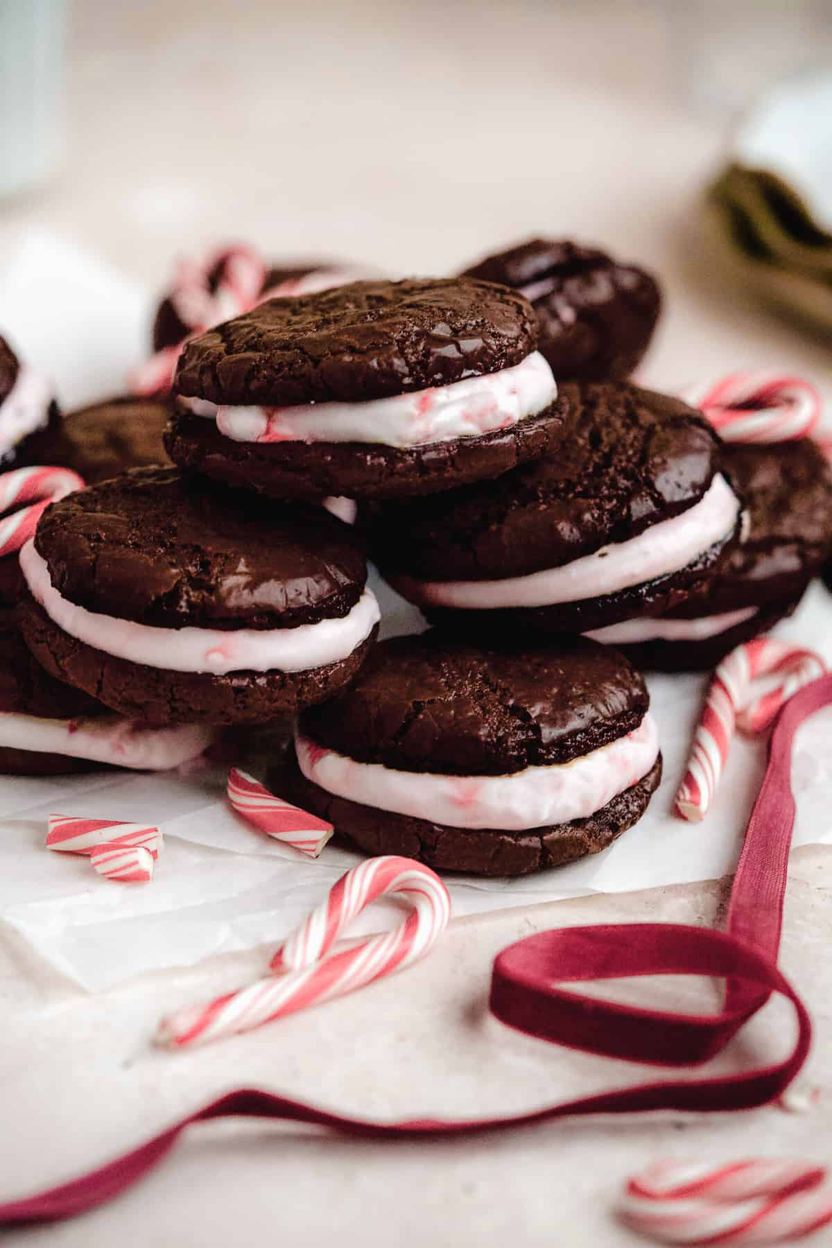 Close up side view of 6 Peppermint Brownie Sandwich Cookies mounded on white parchment paper.