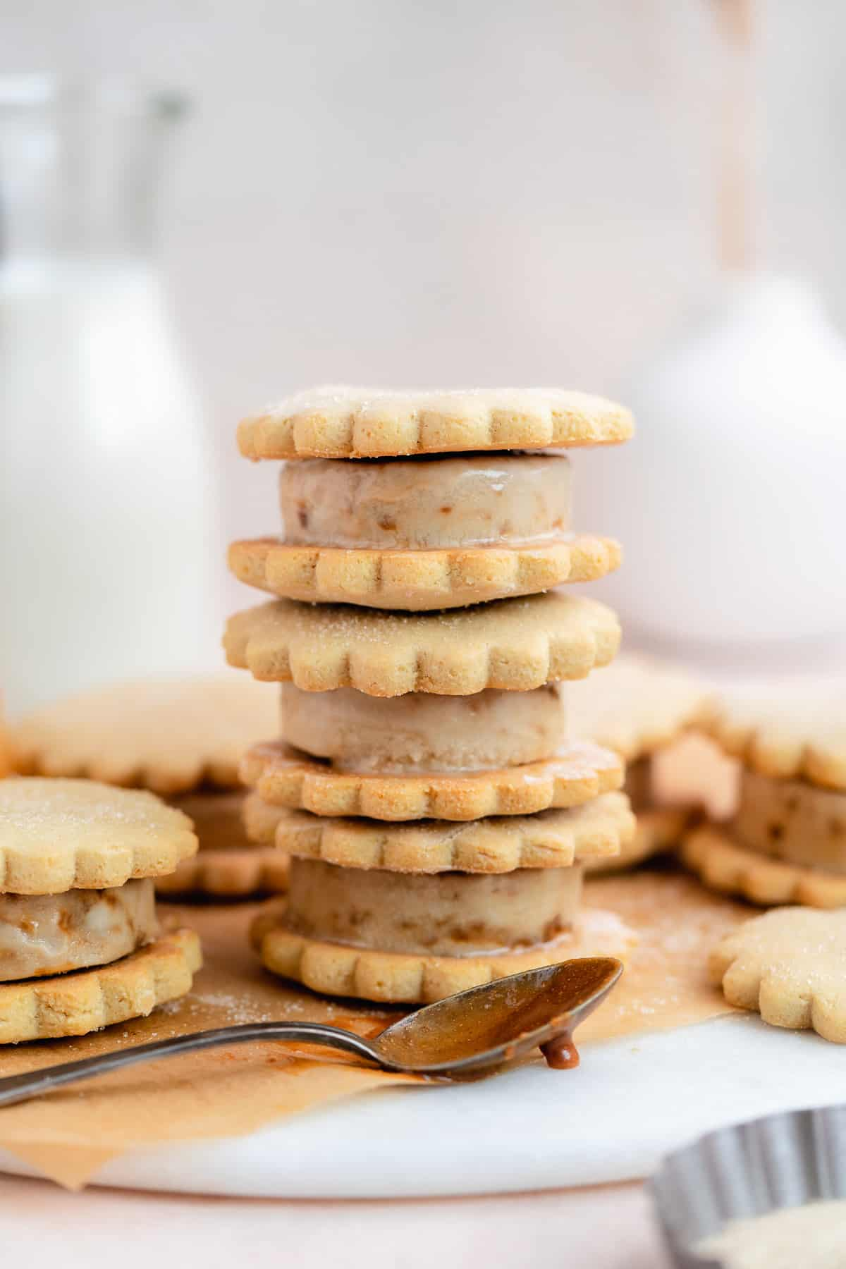 Side view of stack of 3 caramel sugar cookie ice cream sandwiches on parchment paper and marble slab.  One ice cream sandwich and silver spoon dipped in caramel sauce are resting nearby.