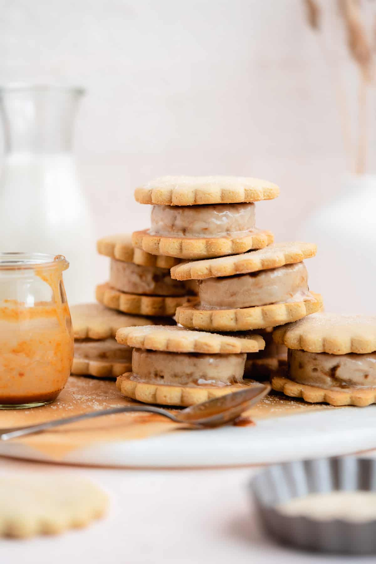 Side view photo of 7 ice cream sandwiches stacked in a pyramid sit on top of parchment paper on a marble slab.   Small clear jar with caramel sauce and silver spoon dipped in caramel sauce are placed nearby.
