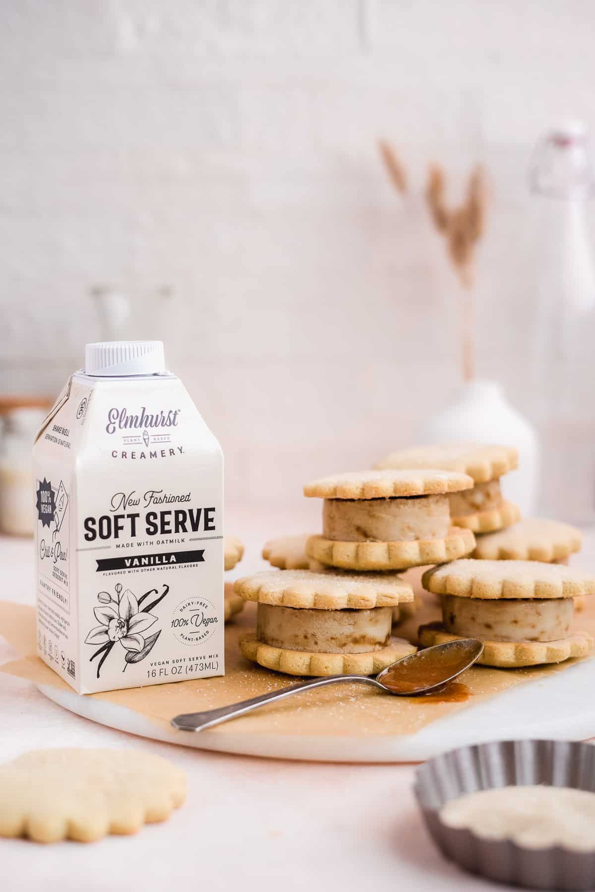 Photo shot from a the side showing multiple stacks of caramel sugar cookie ice cream sandwiches sitting on parchment paper on top of a marble slab.  A carton of Elmhurst's new dairy free ice cream mix and a silver spoon dipped in caramel sauce are placed nearby.