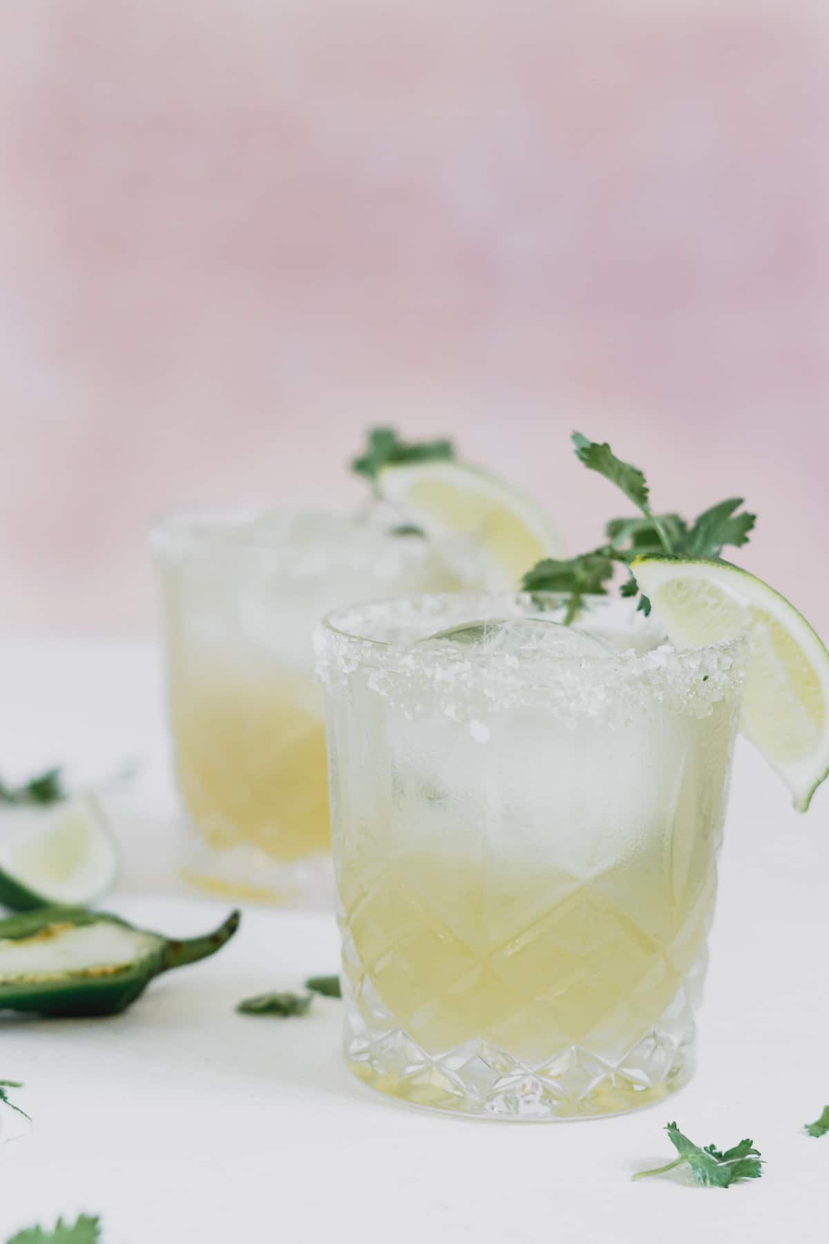 Two glasses full of lime margarita with a lime wedge and green herbs.