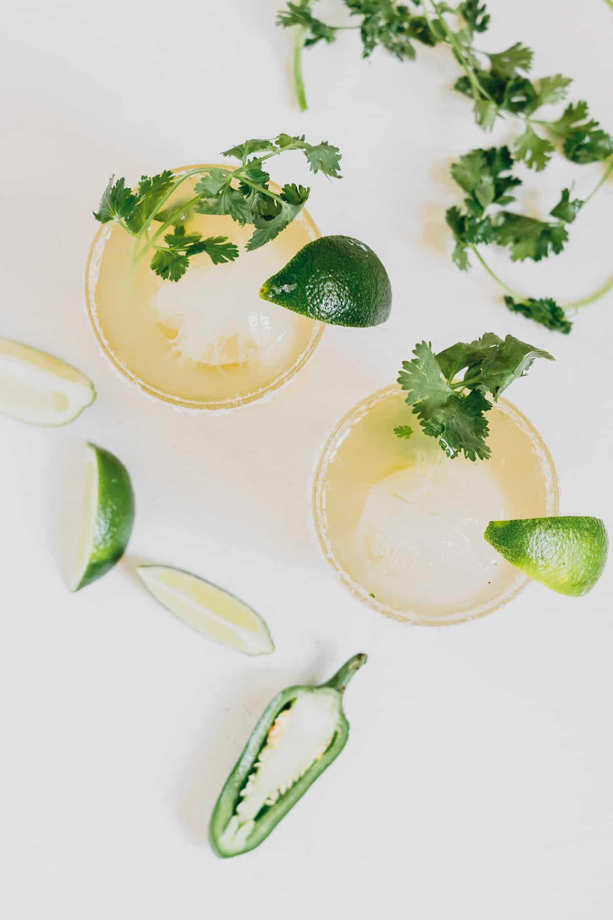 Overhead view of two margaritas in cocktail glasses with lime wedges and fresh cilantro.