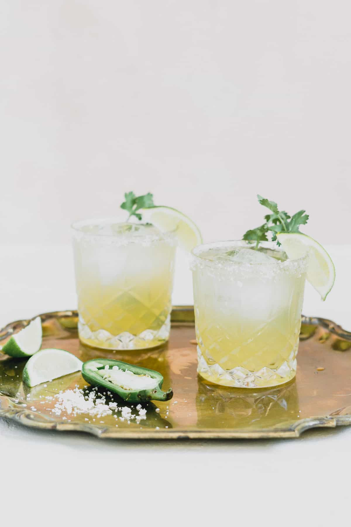 Two margaritas on a gold platter with lime wedges and cilantro.