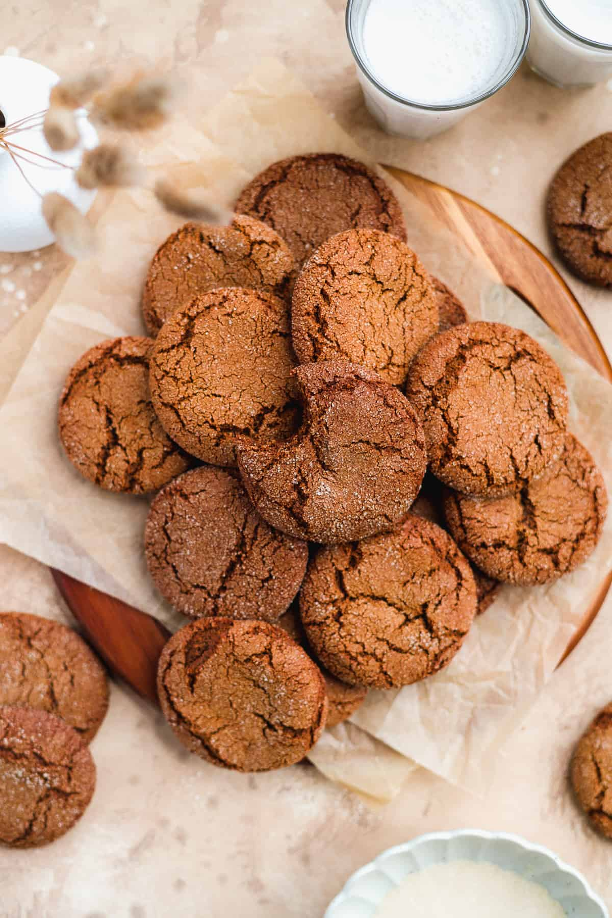 Overhead view of a plate of a dozen freshly baked Soft and Chewy Ginger Snap Cookies on parchment paper on top of a wooden tray.  The top cookie has a bite removed.
