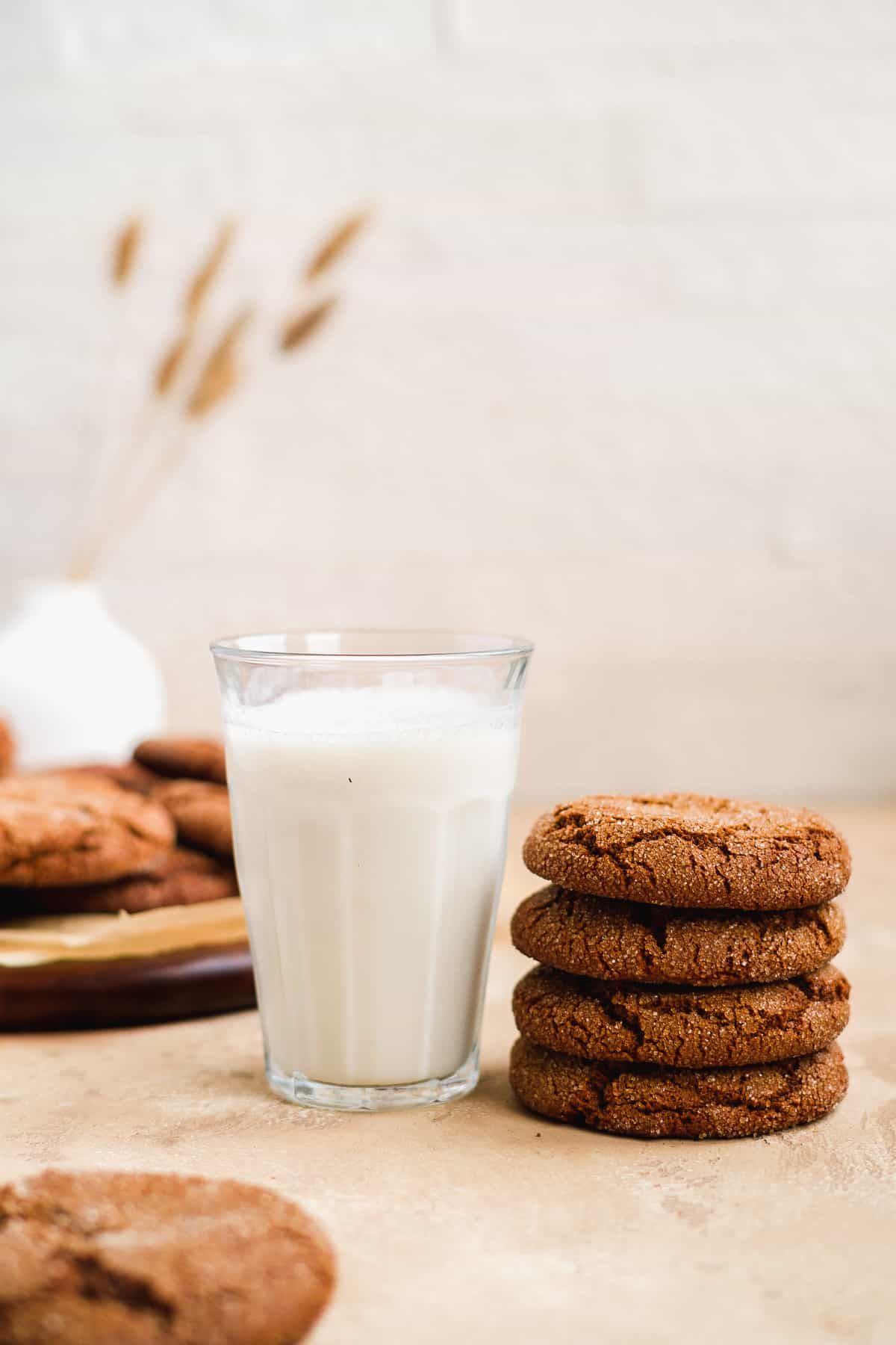 Side view of 4 stacked Soft and Chewy Ginger Snap Cookies sitting next to a cold glass of milk.  A plate of additional cookies is in the background.