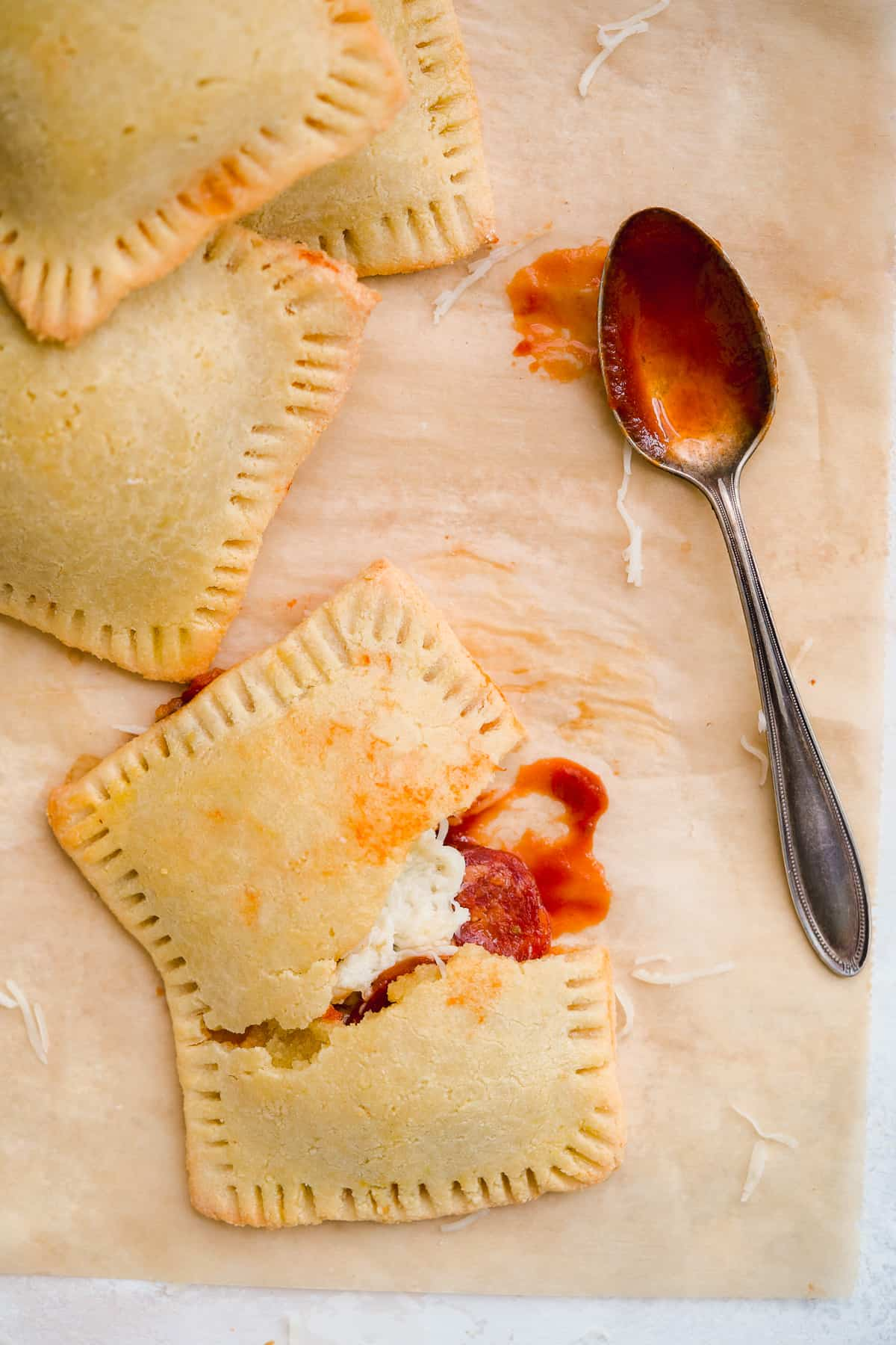 Parchment paper with several pizza hot pockets stacked. One hot pocket is broken in half to reveal yummy filling inside. Silver spoon dipped in marinara is resting nearby. Shredded parmesan cheese is sprinkled around.