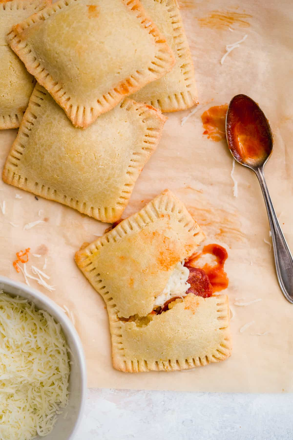 Four yummy pizza hot pockets scattered on brown parchment paper with a bowl of shredded parmesan cheese. One hot pocket is cut in half to reveal delicious insides. Silver spoon with marinara sauce in resting nearby.