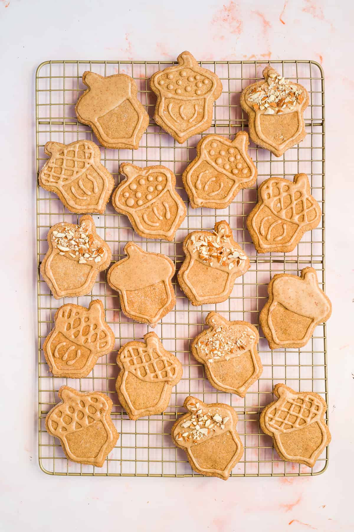 Overhead photo of a full batch of freshly baked Maple Peanut Butter Cut-Out Sugar Cookies on a  gold cooling rack.  Cookies are in the shape of acorns and have been decorated and iced.