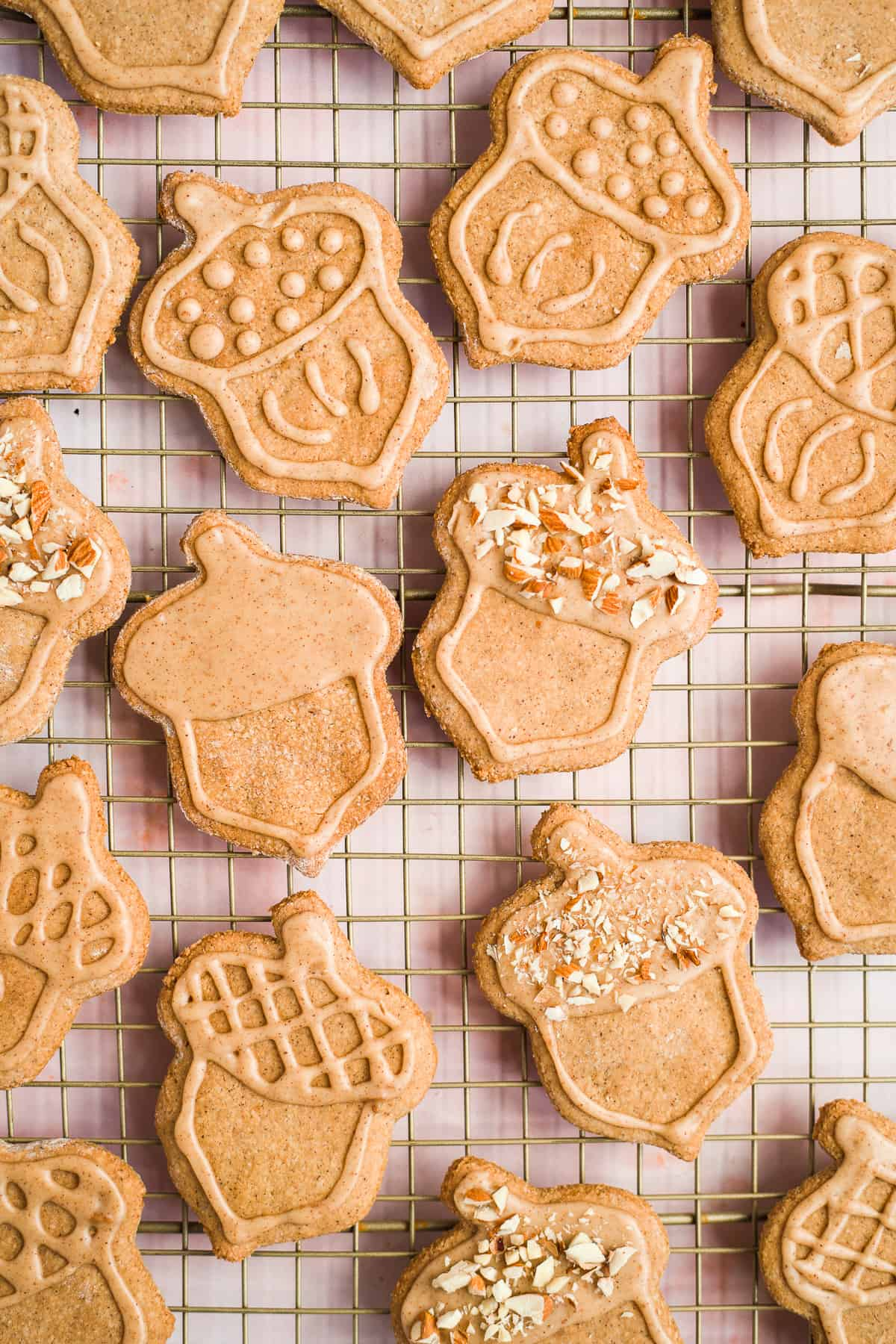 Close up overhead photo of freshly baked and decorated Maple Peanut Butter Cut-Out Sugar Cookies on a cooling rack.