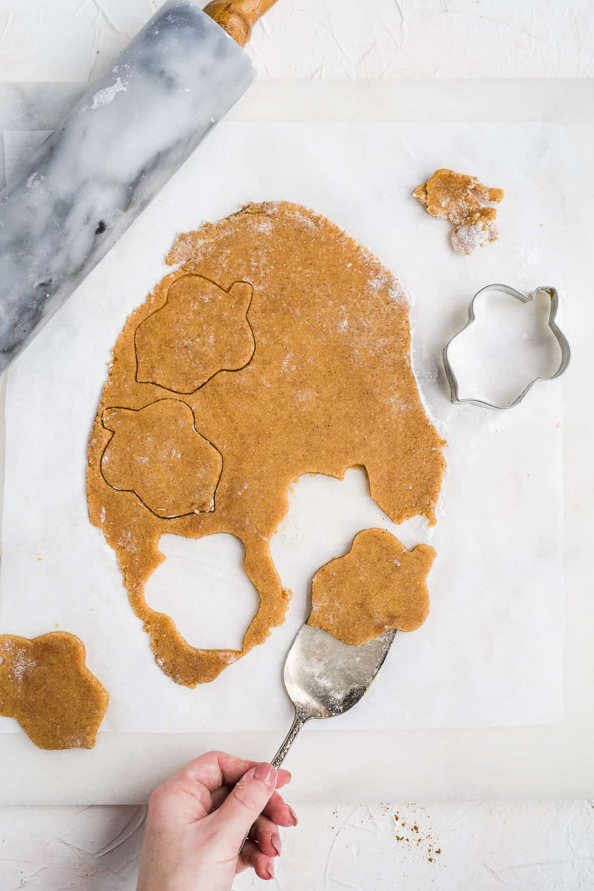 Overhead photo of a recipe step showing the rolled out dough being cut into acorn shaped cookies.  A rolling pin and acorn cookie cutter are nearby.