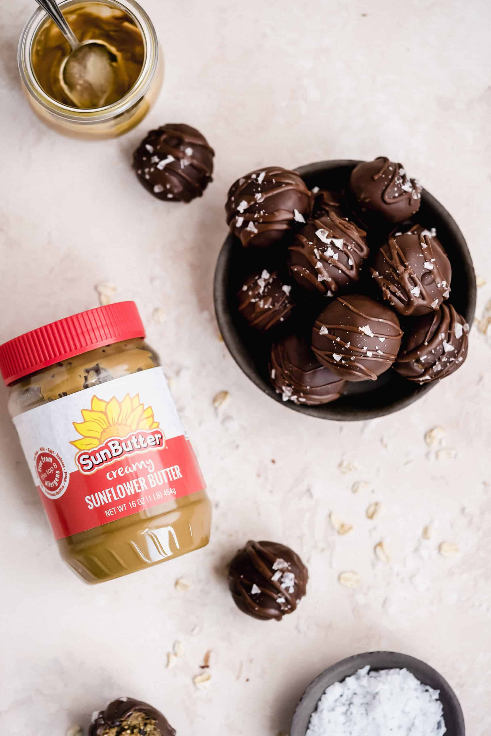 Overhead photo of a bowl of Oatmeal Chocolate Chip Cookie Dough Bites with a jar of SunButter Creamy Sunflower Butter laying nearby.