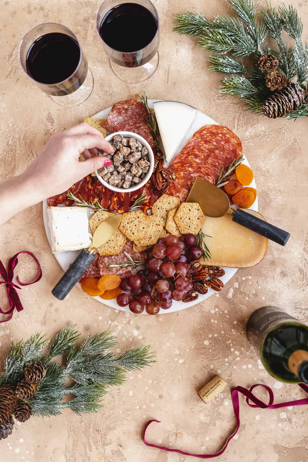 Overhead photo of round white marble cake platter filled with assorted meats, cheeses, fruits, crackers and nuts.  Two glasses of red wine sit nearby.  Hand is reaching to pick up some nuts from the charcuterie board.