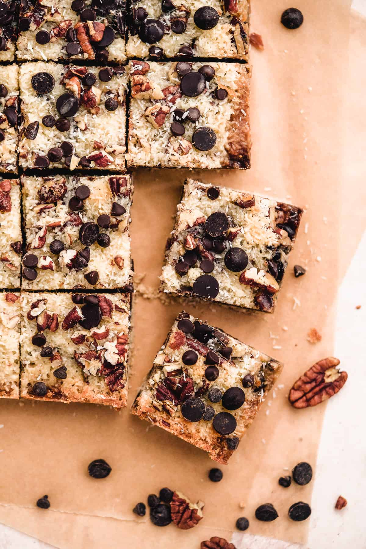 Overhead view of freshly baked Toasted Oat Seven Layer Magic Cookie Bars cut into squares.  Pecans and chocolate chips are sprinkled around.
