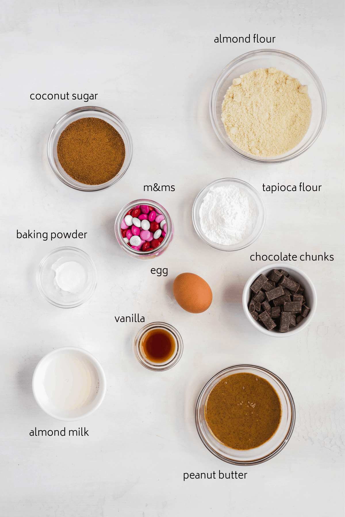 Image of ingredients labeled in glass bowls on a white surface.