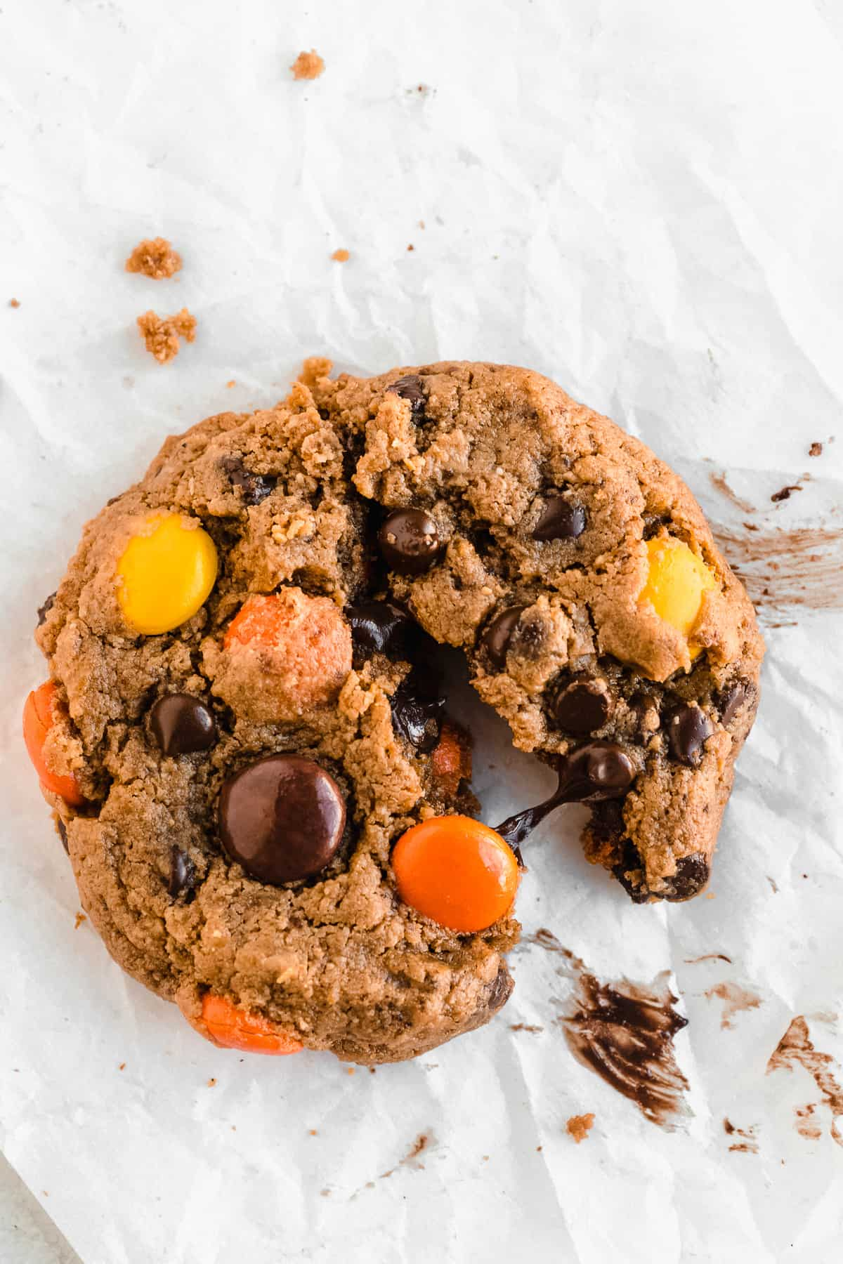 Cookie pulled apart with chocolate in the middle and Reece's pieces on top on a white backdrop.