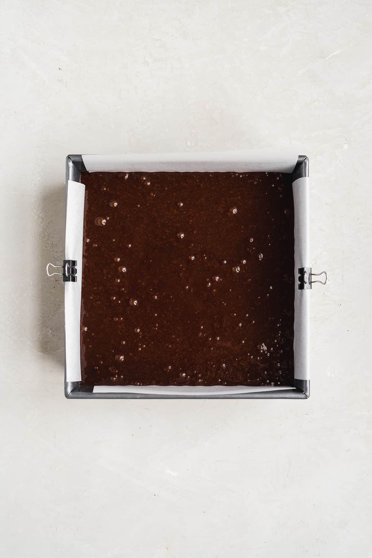Baking pan filled with chocolate brownie batter on a white surface.