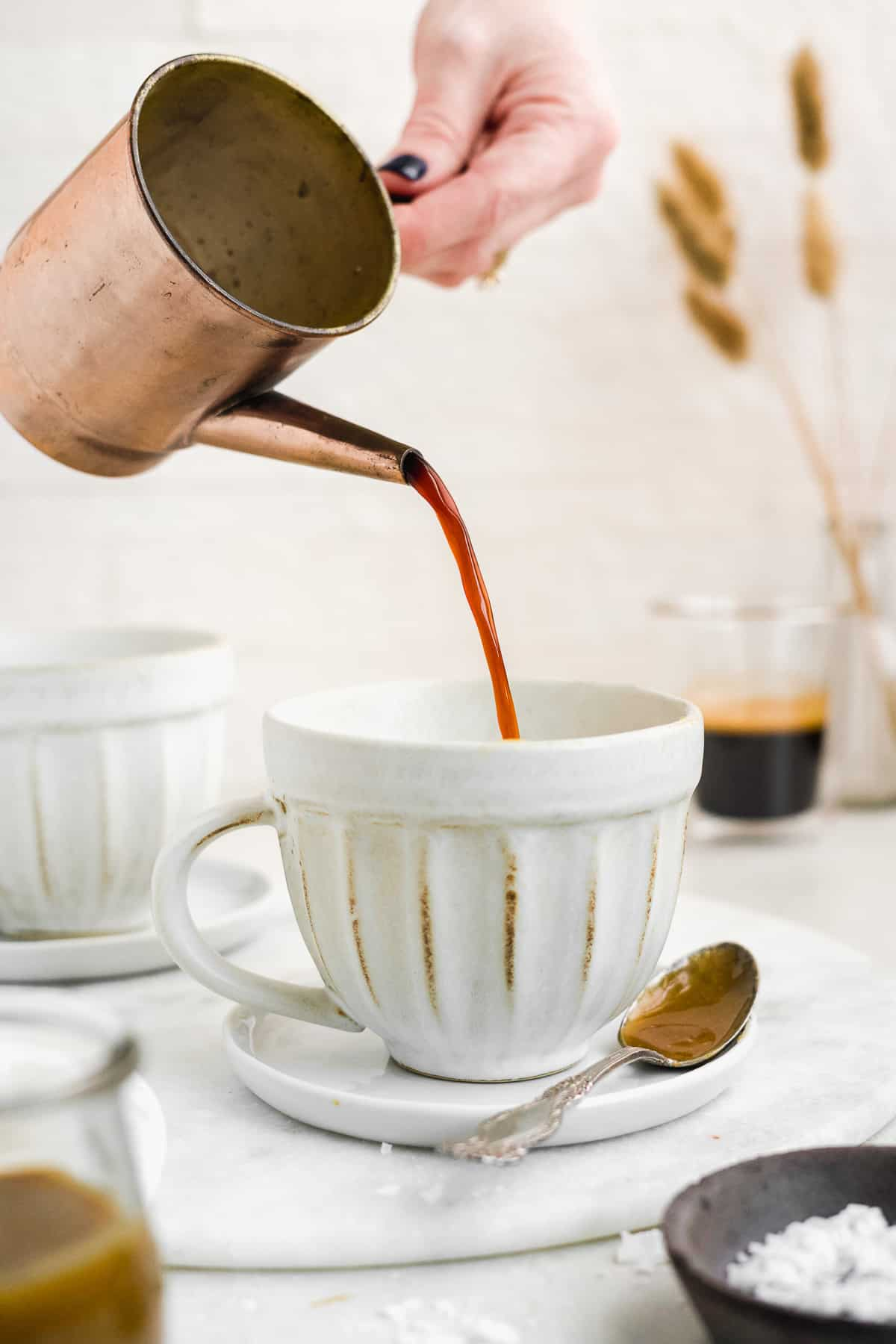 Hand pouring espresso into a coffee mug on a white surface.