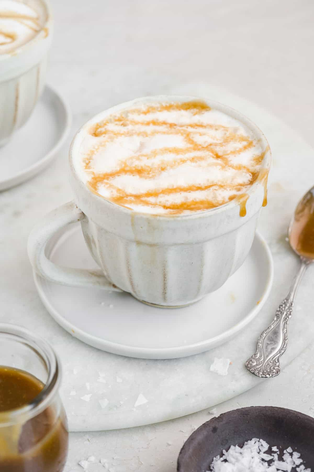 White coffee mug with frothed milk and caramel drizzled on top on a white background.