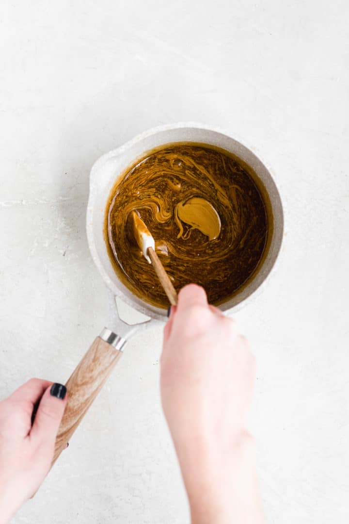 Hand mixing caramel sauce in a pot on a gray surface.