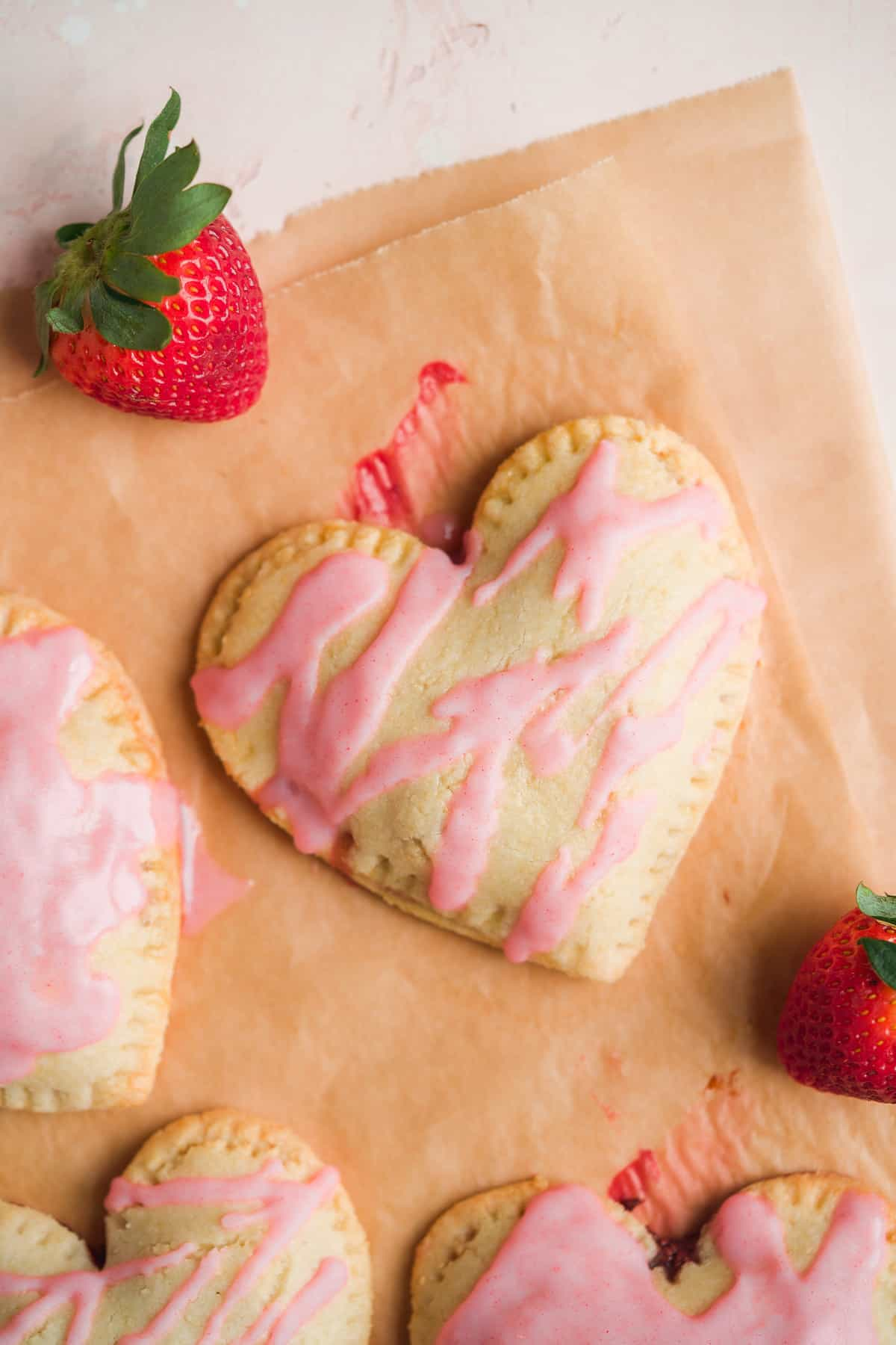 Heart shaped pop tart on brown parchment paper with pink icing and strawberries in the corner