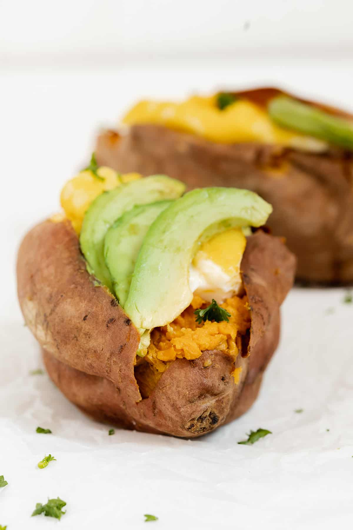 Front view of a stuffed sweet potato with avocado slices and herbs.