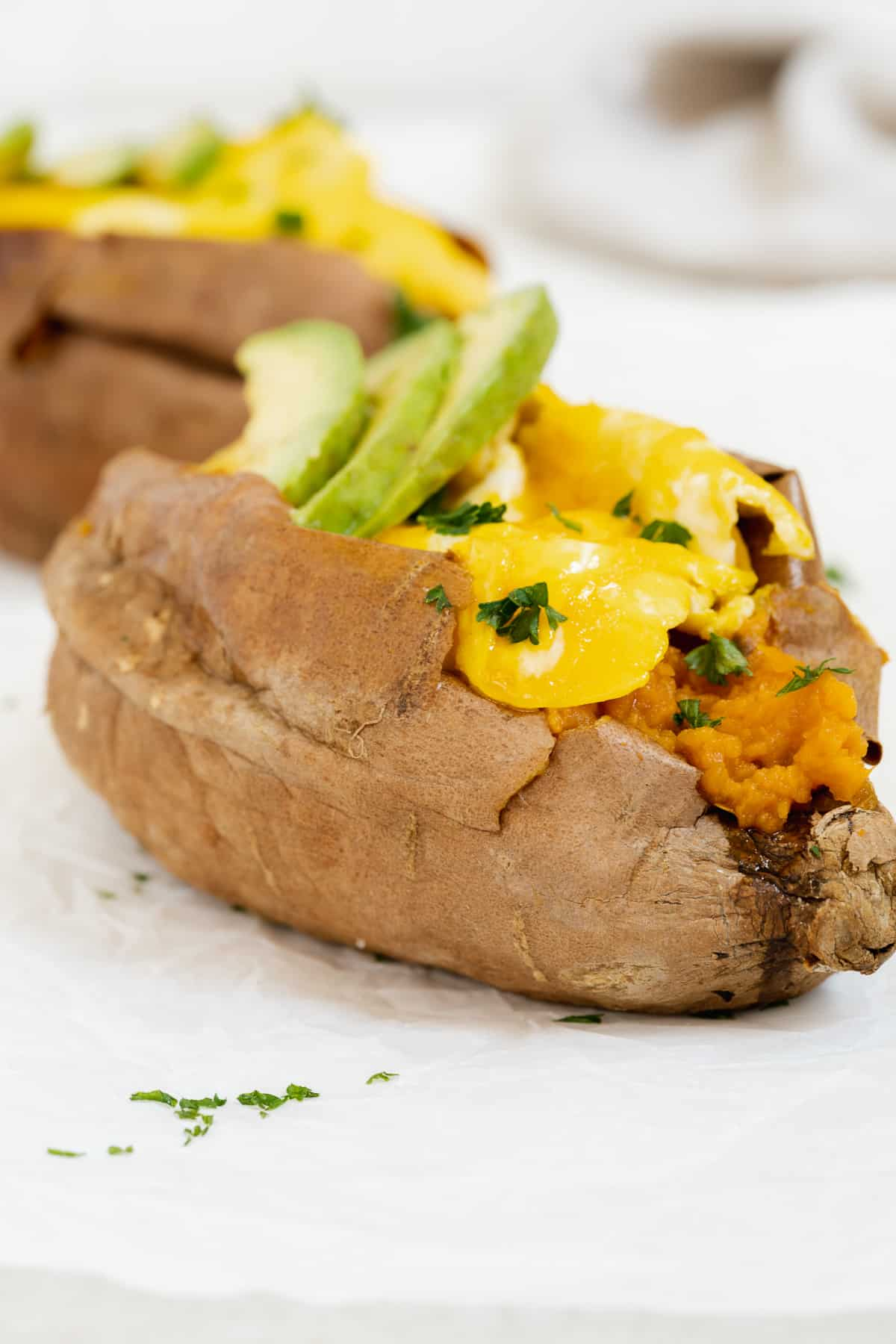 Sweet potato cup open with scrambled egg and herbs on a white surface.