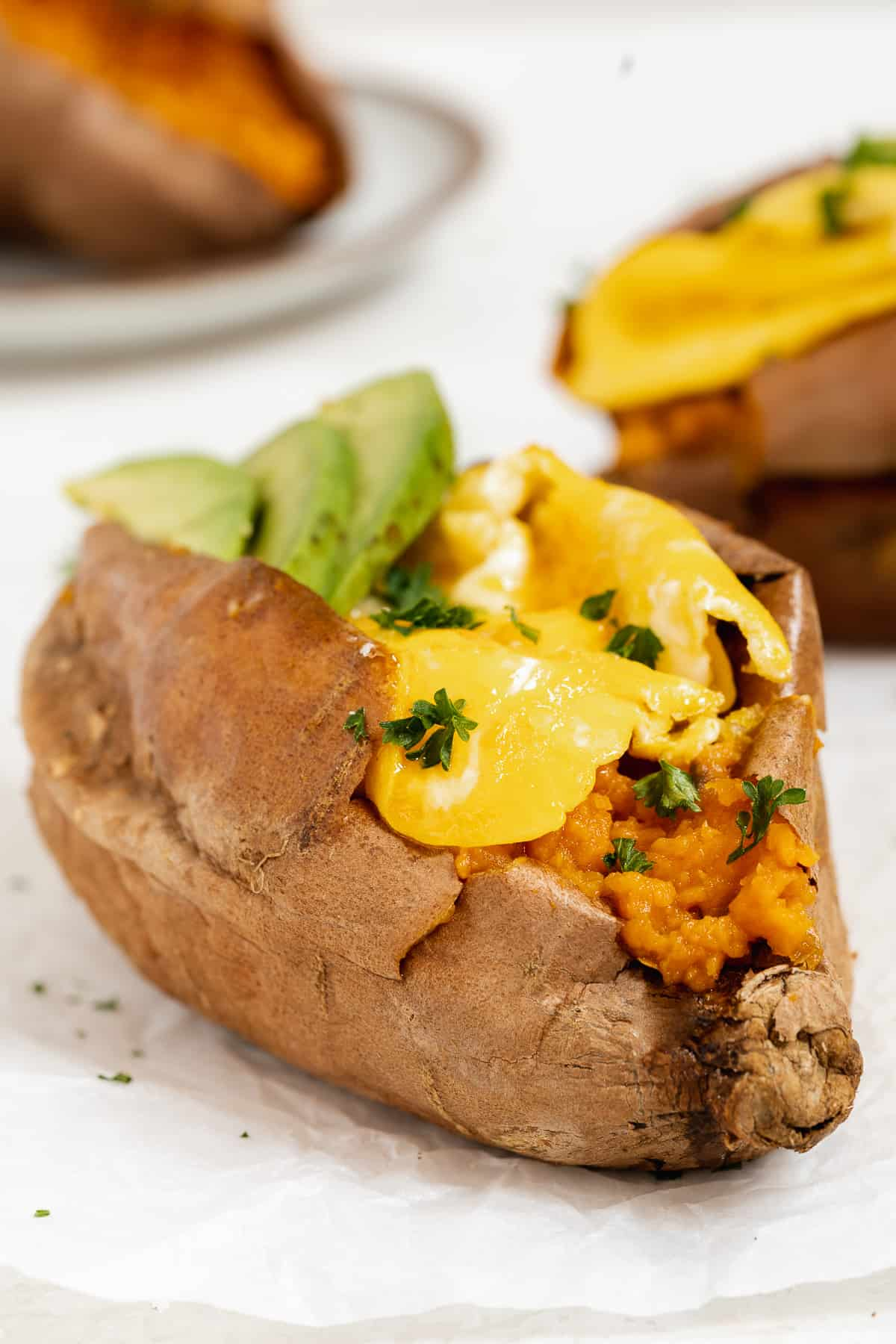 Sweet potato stuffed with a scrambled egg with green herbs and avocado on a white surface.