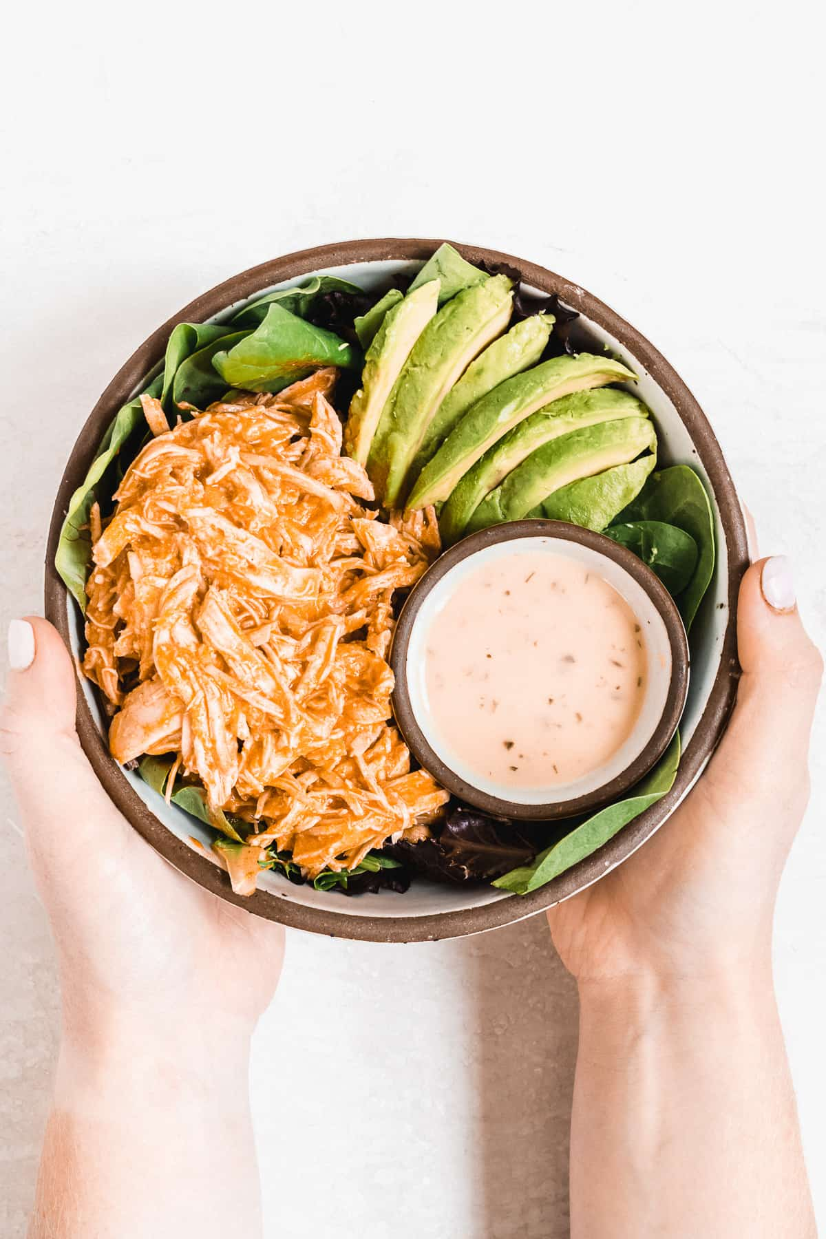 Two hands holding bowl full of buffalo chicken, avocado slices, and dressing.