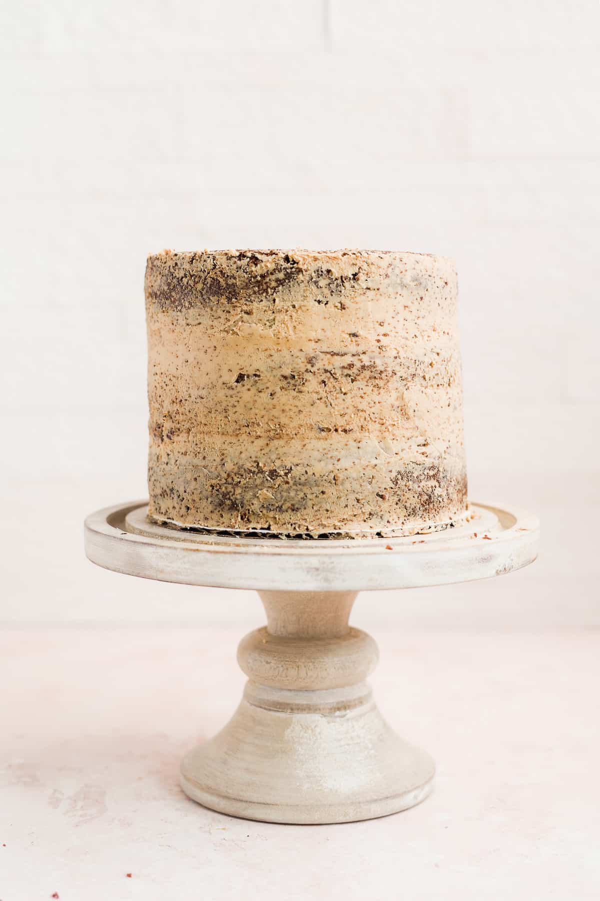 Cake on a stand with crumb coat on a pink surface.