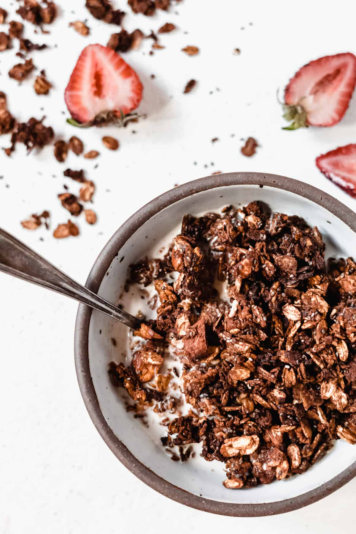 Bowl full of granola with a spoon in it and strawberries on the ground.
