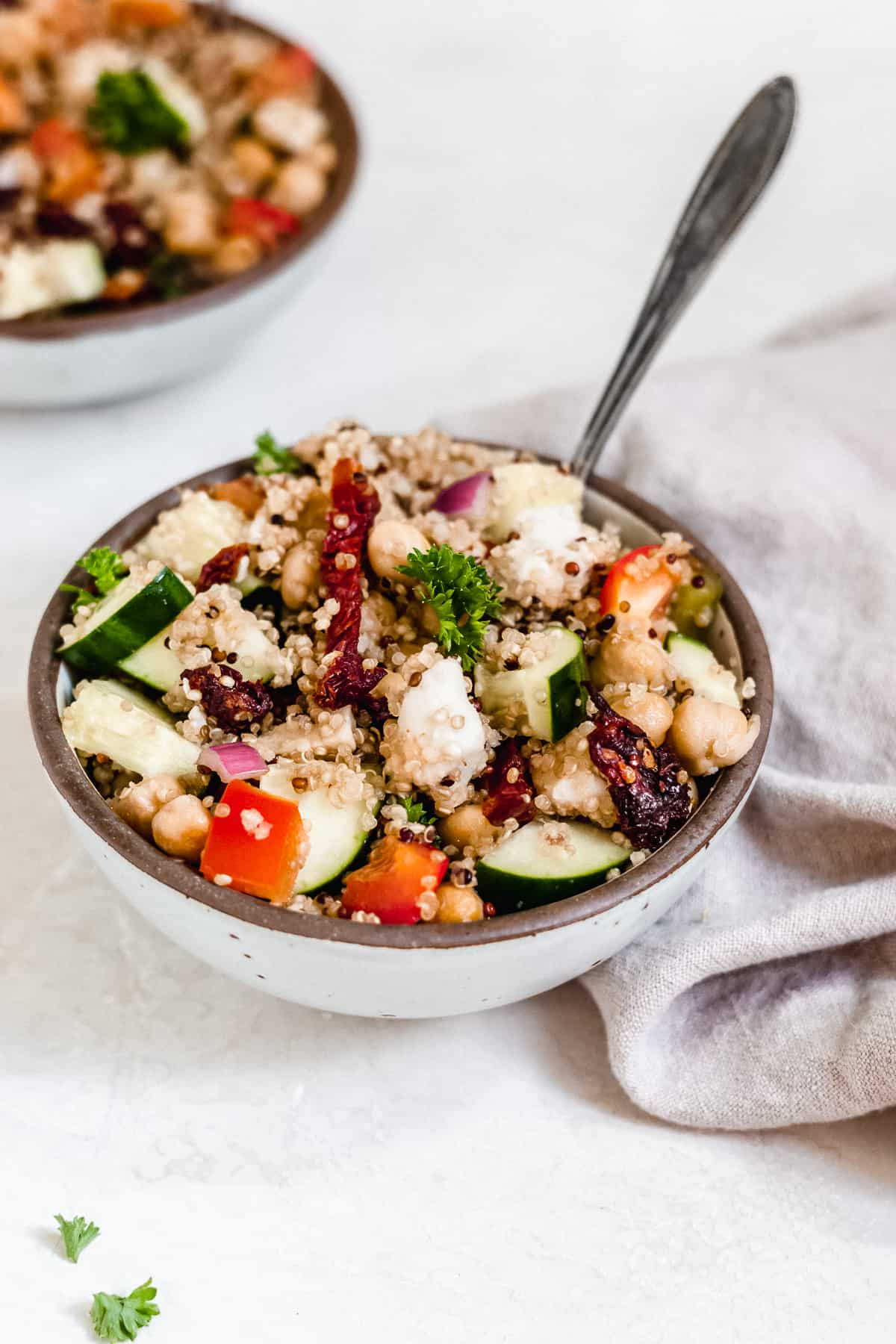 White bowl full of quinoa salad with cucumbers and red peppers on a white surface.