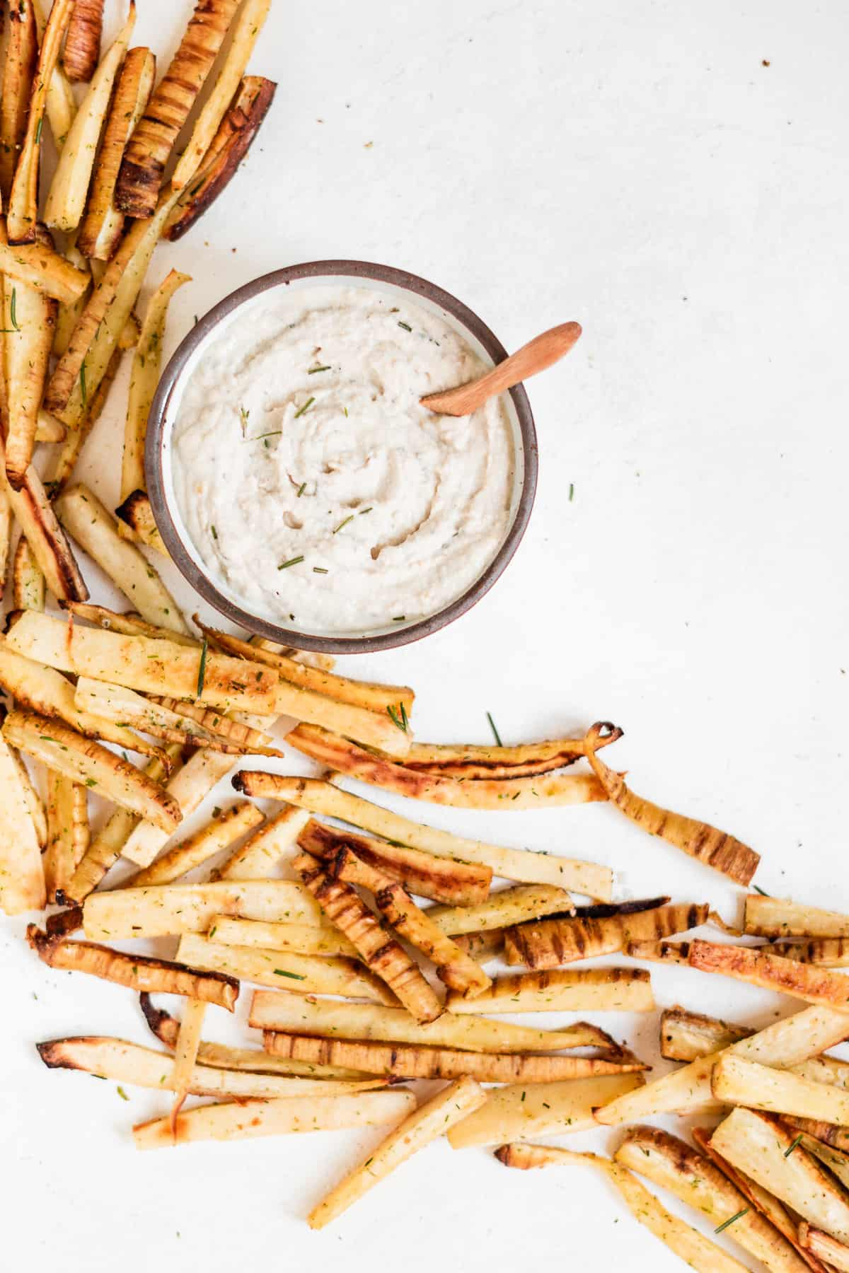 Bowl of aioli dip with parsnip fries on the surface.