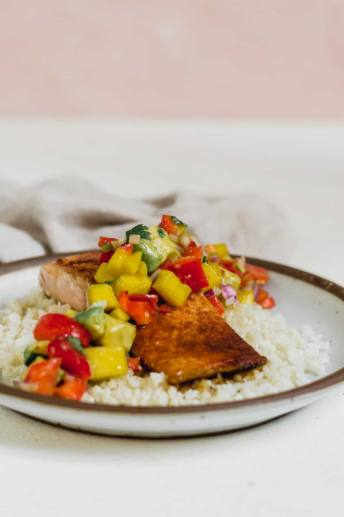 Side view of a dinner plate with rice and salmon topped with avocado and mango salsa.