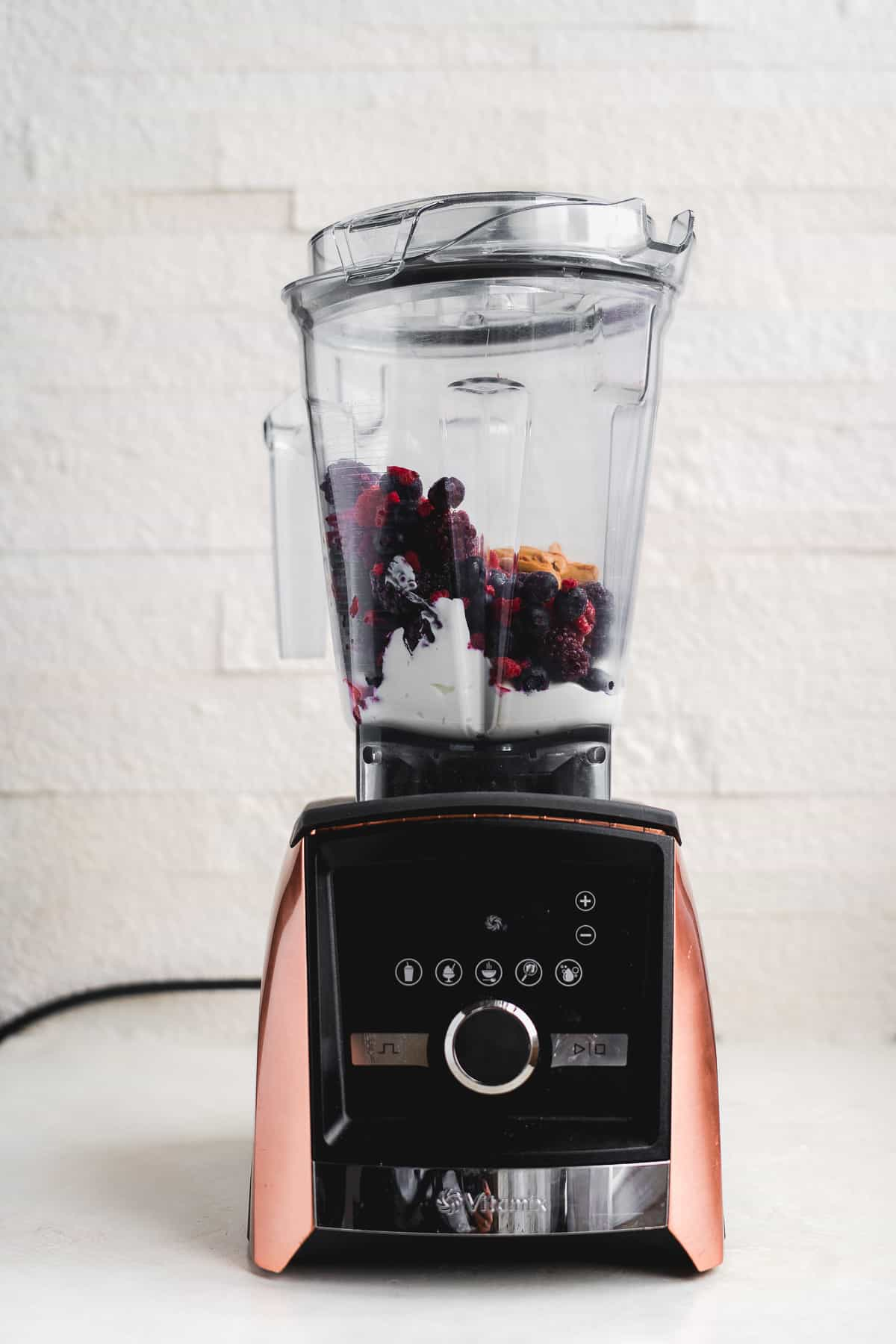 Blender with smoothie ingredients in front of a white backdrop.