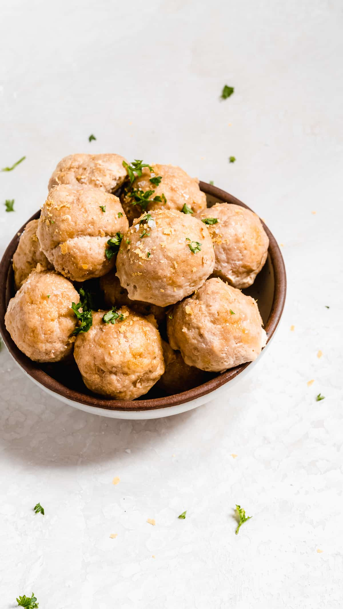 Brown bowl of turkey meatballs with green herbs on a white surface.
