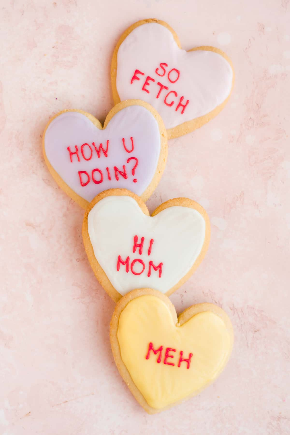 Four heart shaped sugar cookies with pastel icing and red writing in a line on a pink surface.