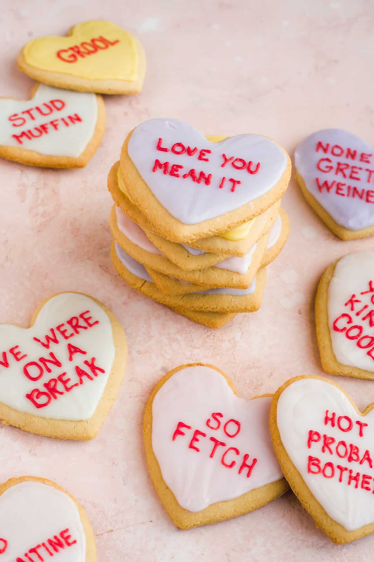 A stack of heart sugar cookies with cookies scattered beneath.