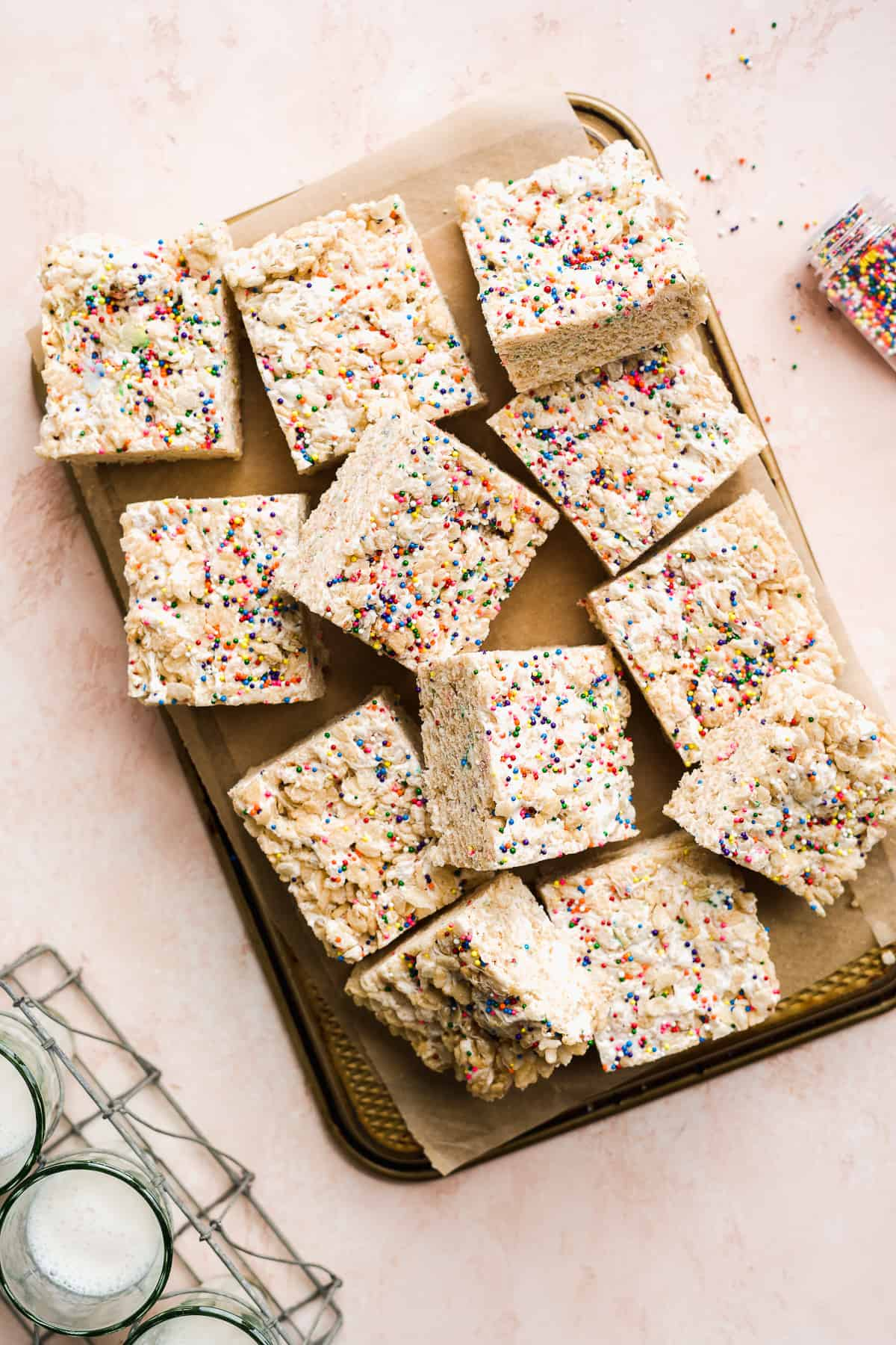 Rice krispie treats with sprinkles cut into squares on top of an upside down baking pan