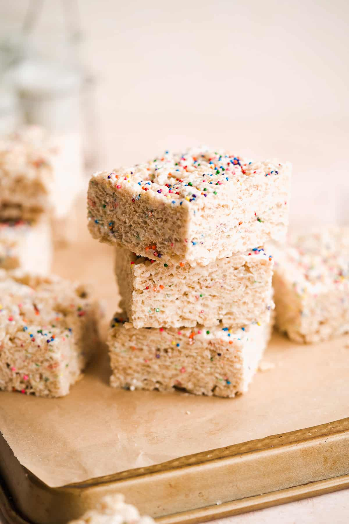 3 rice krispie treats with sprinkles stacked on tan parchment paper.