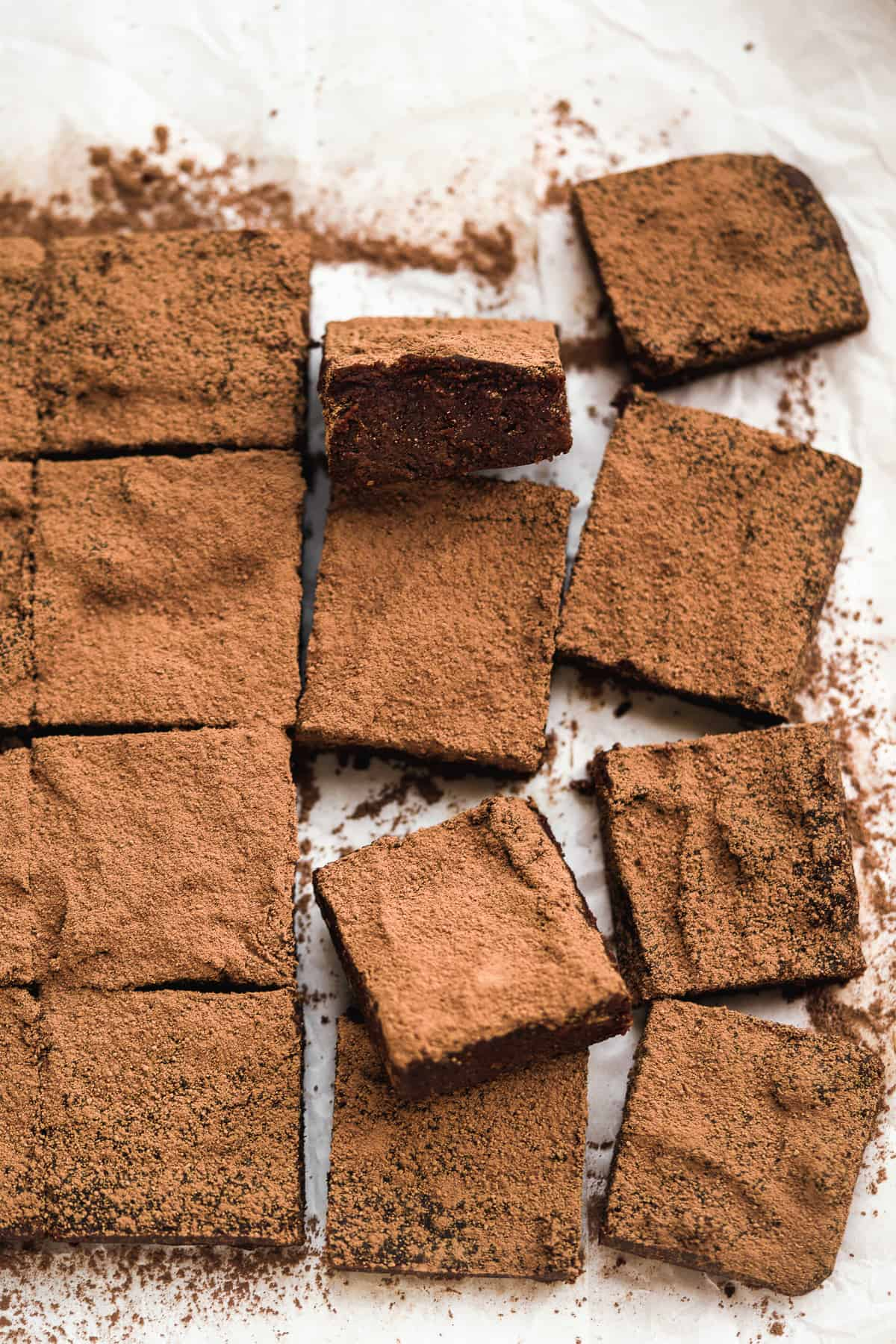 Line of brownies sliced into squares on a white piece of paper.
