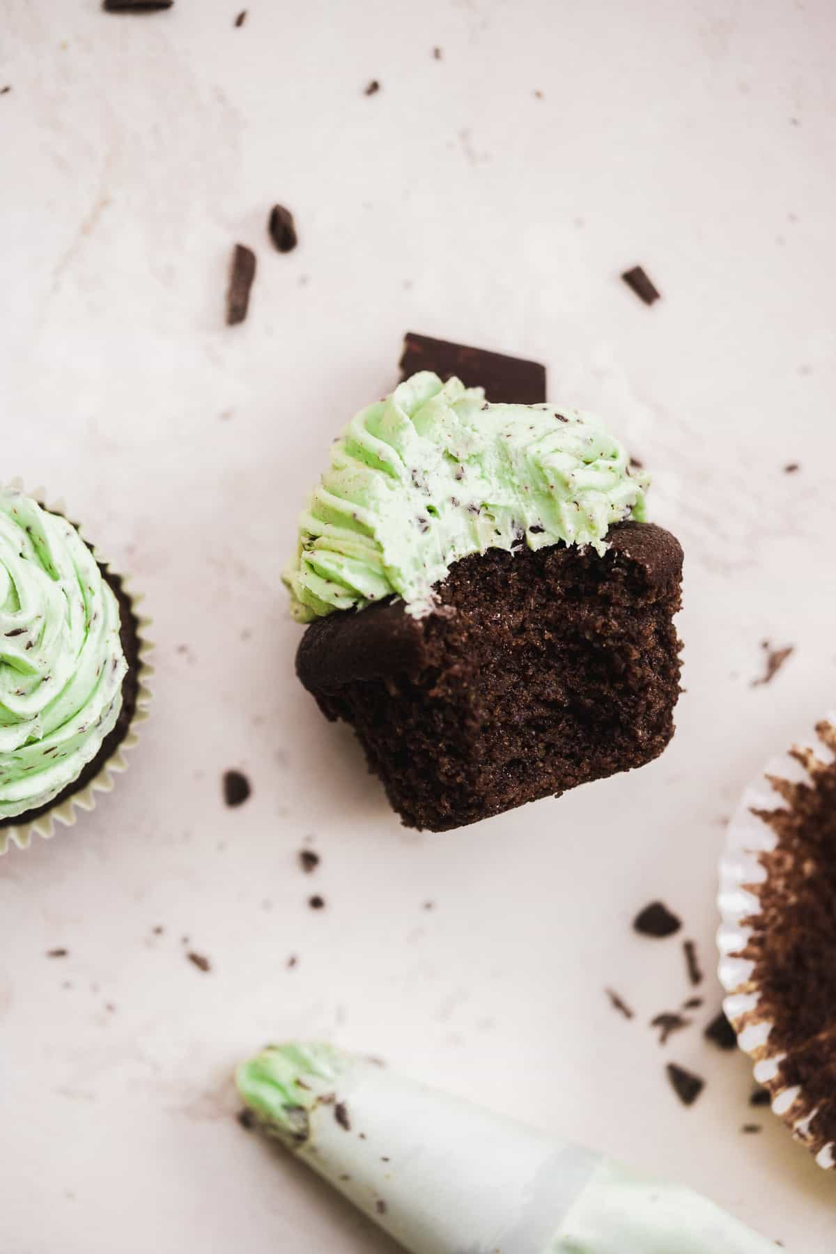 Image of a chocolate cupcake on a cream surface with a bite taken out of it and green frosting.