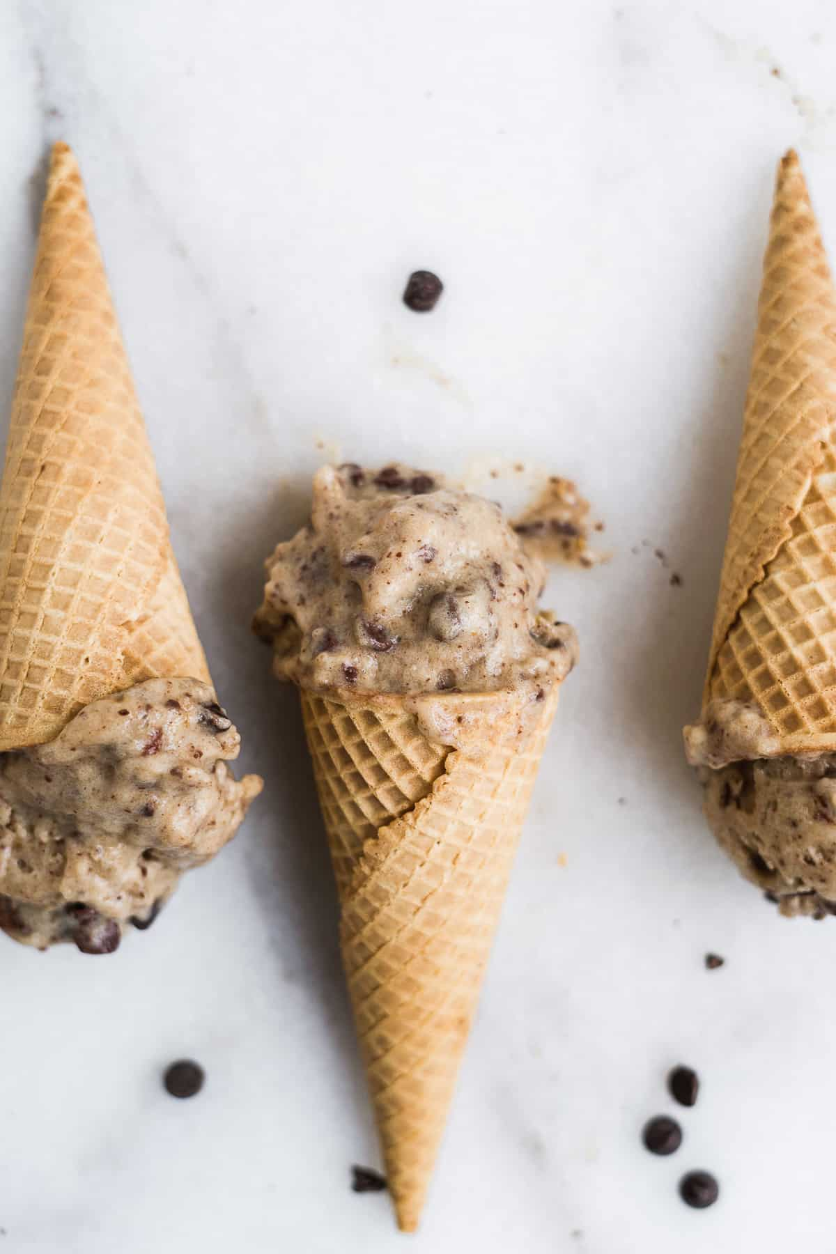 Ice cream cones laying on a marble surface with banana ice cream.