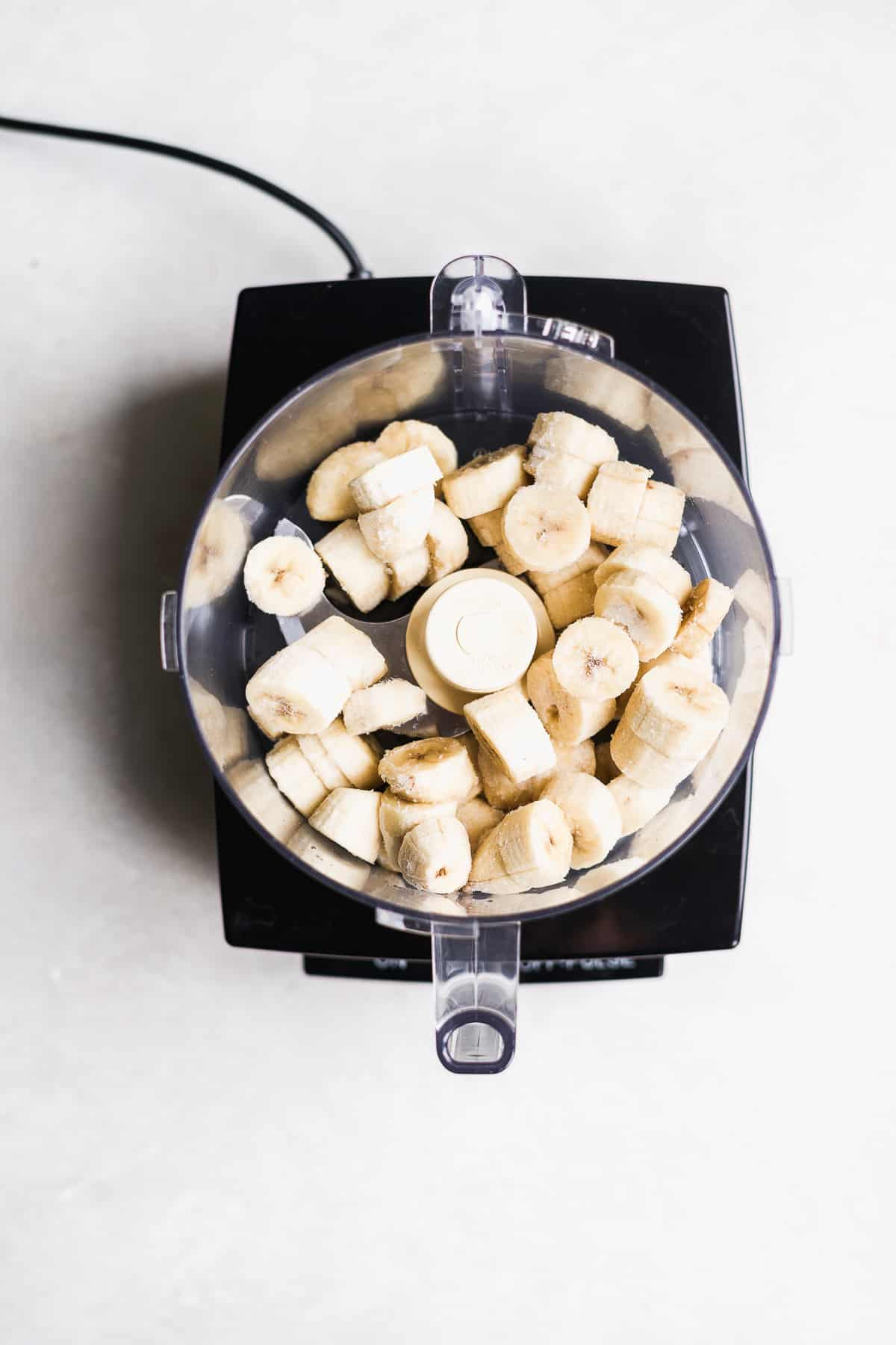 Frozen banana slices in a food processor on a white surface.