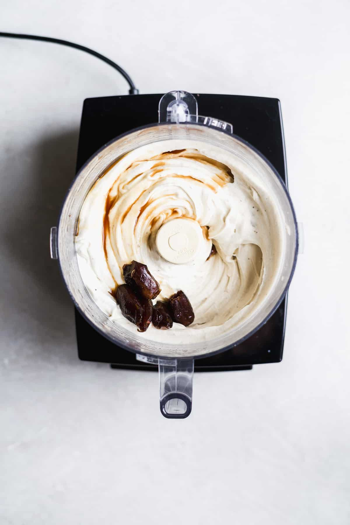 Banana ice cream blended in a food processor with dates about to be mixed in.