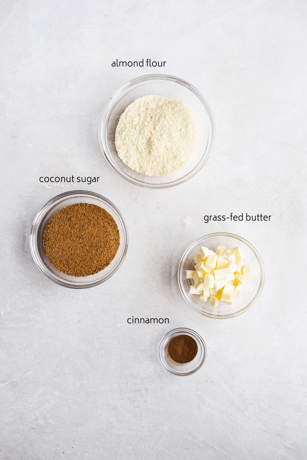 Image of streusel ingredients in glass bowls on a white surface with black labels.