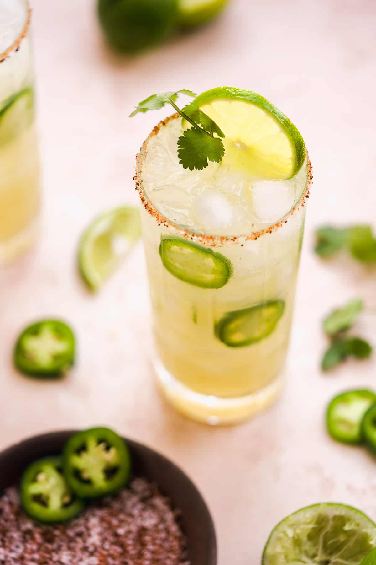 Tall salted cocktail glass filled with a lime green margarita and a lime wedge and cilantro stem on top.